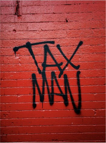 red wall with black letters tax man