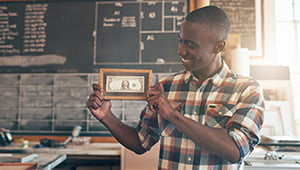 Proud young African business owner showing off the very first dollar bill his business ever earned, showing the value of investing in small business growth